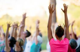 hands raised of people doing yoga in a park